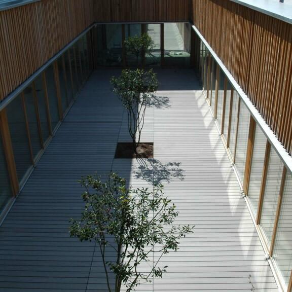 Innenhof mit WPC Terrassendielen und Holzfassade an einer Schule