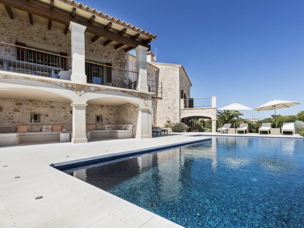 Villa aus Naturstein mit WPC Außendielen, Pool und gemütlicher überdachter Sitzfläche