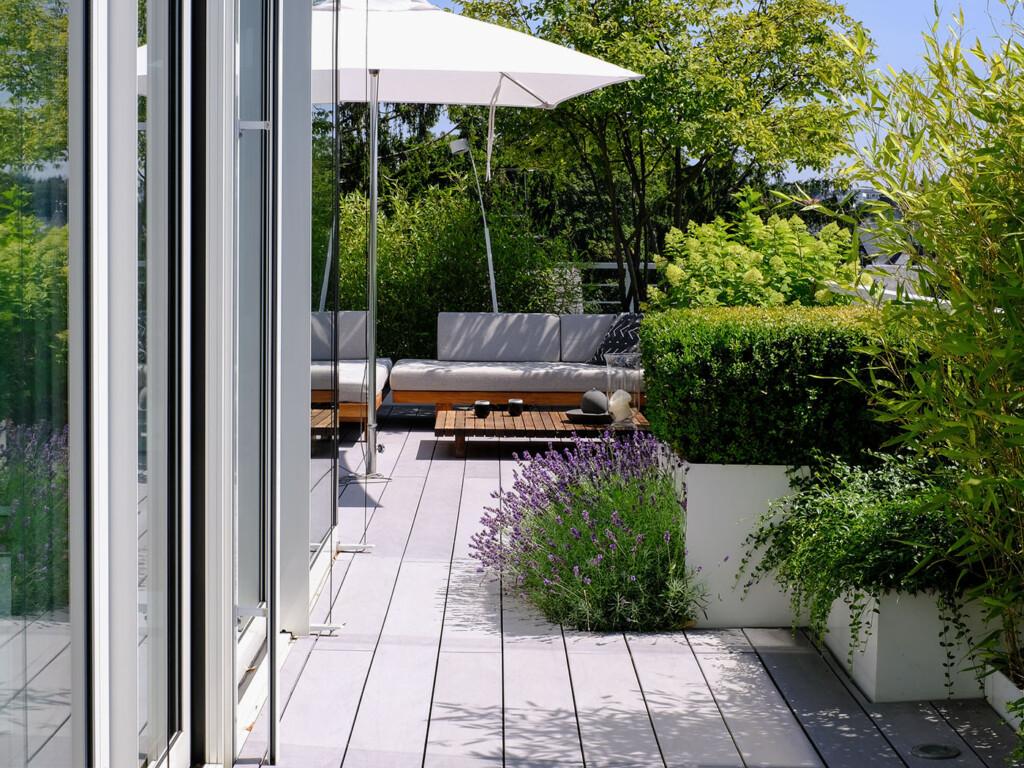 Moderner Balkon mit Balkondielen aus WPC von MYDECK und viel Balkonpflanzen und Sitzecke