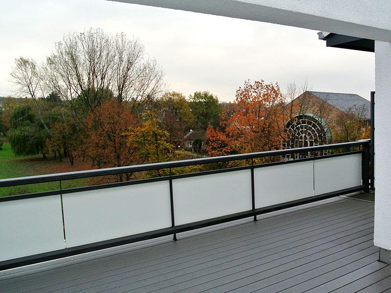 Pflegeleichter Balkonboden aus WPC von MYDECK nach Regen. Balkon mit Park-Ausblick.