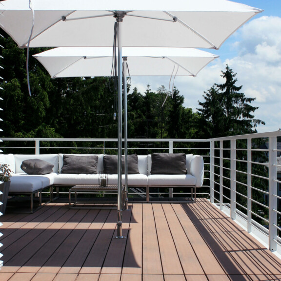 Moderner Balkon mit Sonnenschirmen und bildschönen dunkelbraunen Balkondielen - moderne Balkongestaltung
