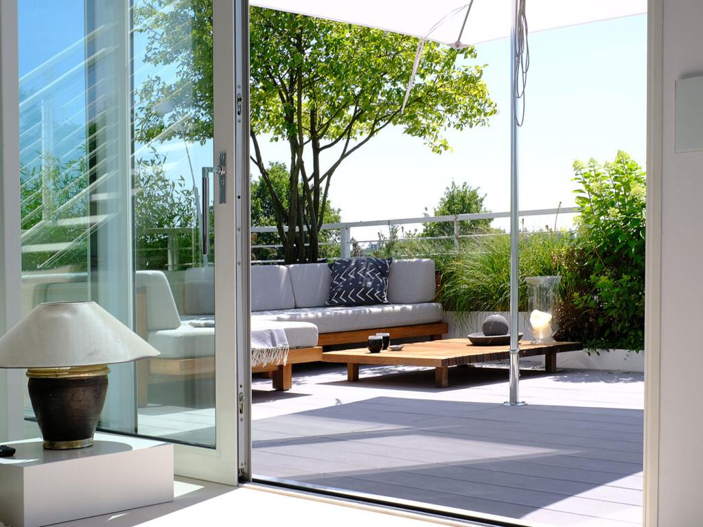 Gemütliche Sitzecke auf modernen Balkon mit grauen WPC Balkondielen und umliegender Begrünung