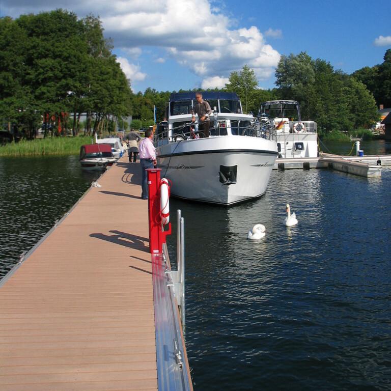 Blick auf Bootssteg mit Massivdielen in hellbraun als Belag für die Bootsstege der Marina Tor zur Müritz bei Sonnenschein