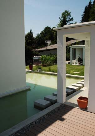 Wasserfläche um modernes Haus herum mit Poolumrandung aus bildschönen WPC Terrassendielen