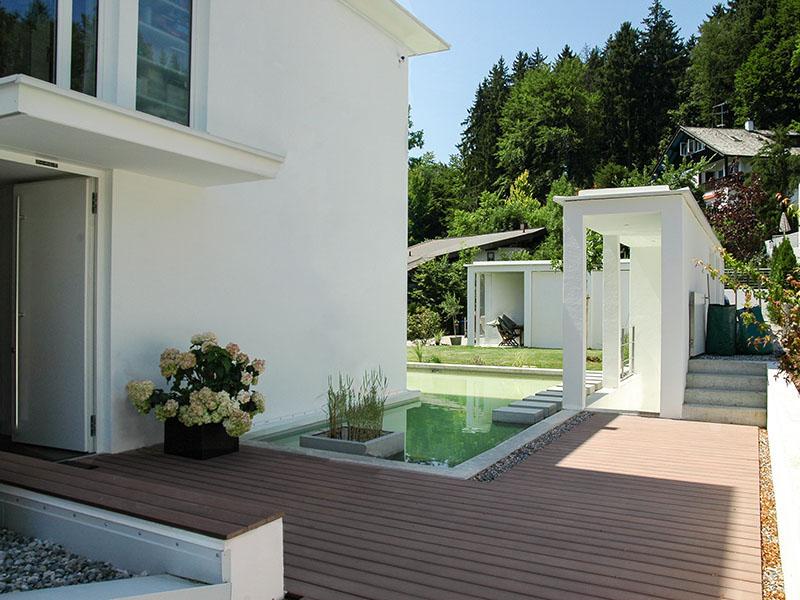 Modernes Holz mit modernem Holzboden aus Holz und Polyethylen, Wasserfläche vor Haus