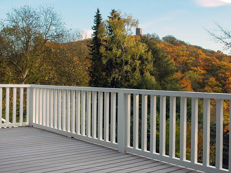 Terrasse mit modernem Holzboden aus Holz und Polyethylen, weißes Geländer, Bäume in Herbststimmung