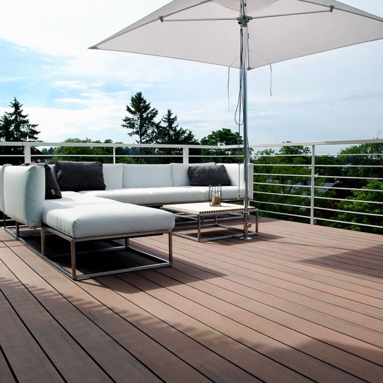 Balkon mit moderner langlebiger Holzterrasse in braun und modernen Balkonmöbeln