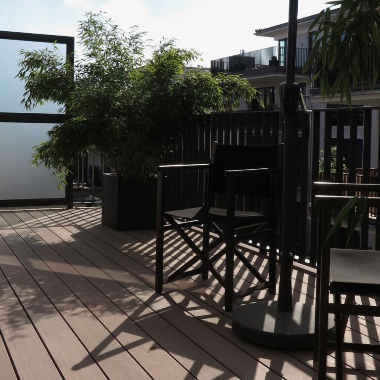 Balkongestaltung mit dunkelbraunem WPC Balkonbelag und mattierter Glasscheibe zur Abtrennung zum nächsten Balkon