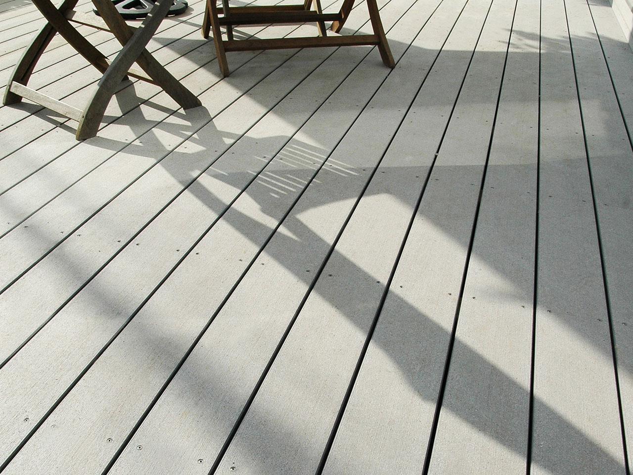 Hellgrauer Bodenbelag auf Balkon im Sonneschein mit Schattenwurf von Gartenmöbeln (Detailausschnitt)
