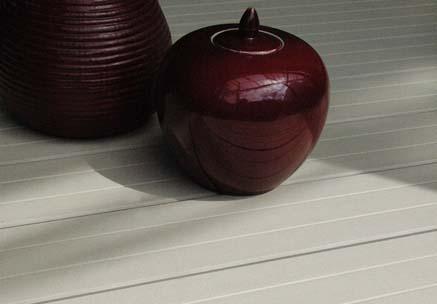 Moderne Holzdielen aus WPC (Holz und Polyethylen) im Sonnenschein mit roten Dekovasen