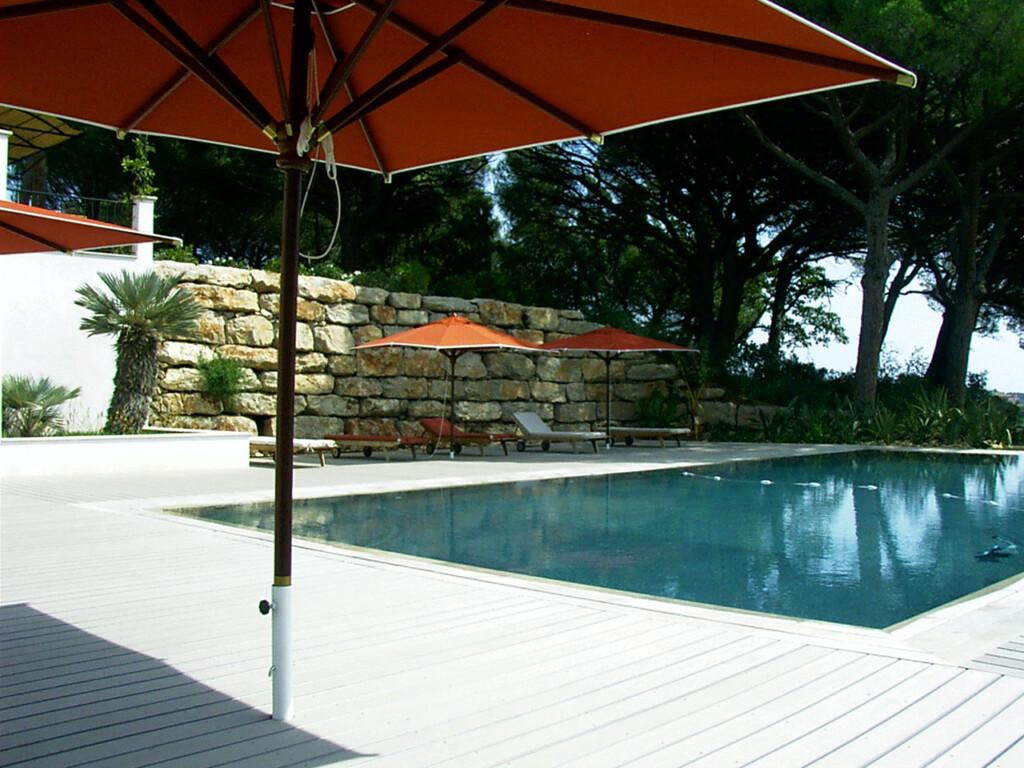 Blick auf mediterranen Pool mit WPC Pooldielen als Umrandung, sowie Natursteinmauer und roter Sonneschirm
