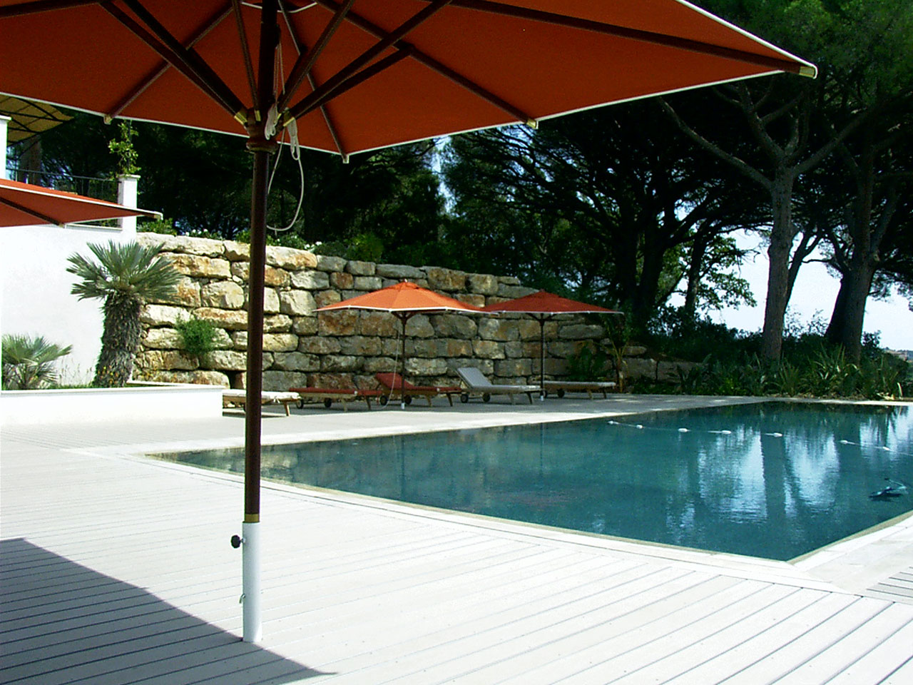 Poolumrandung aus WPC Pooldielen mit Sonneschirmen darauf und Blick auf mediterranes Ambiente