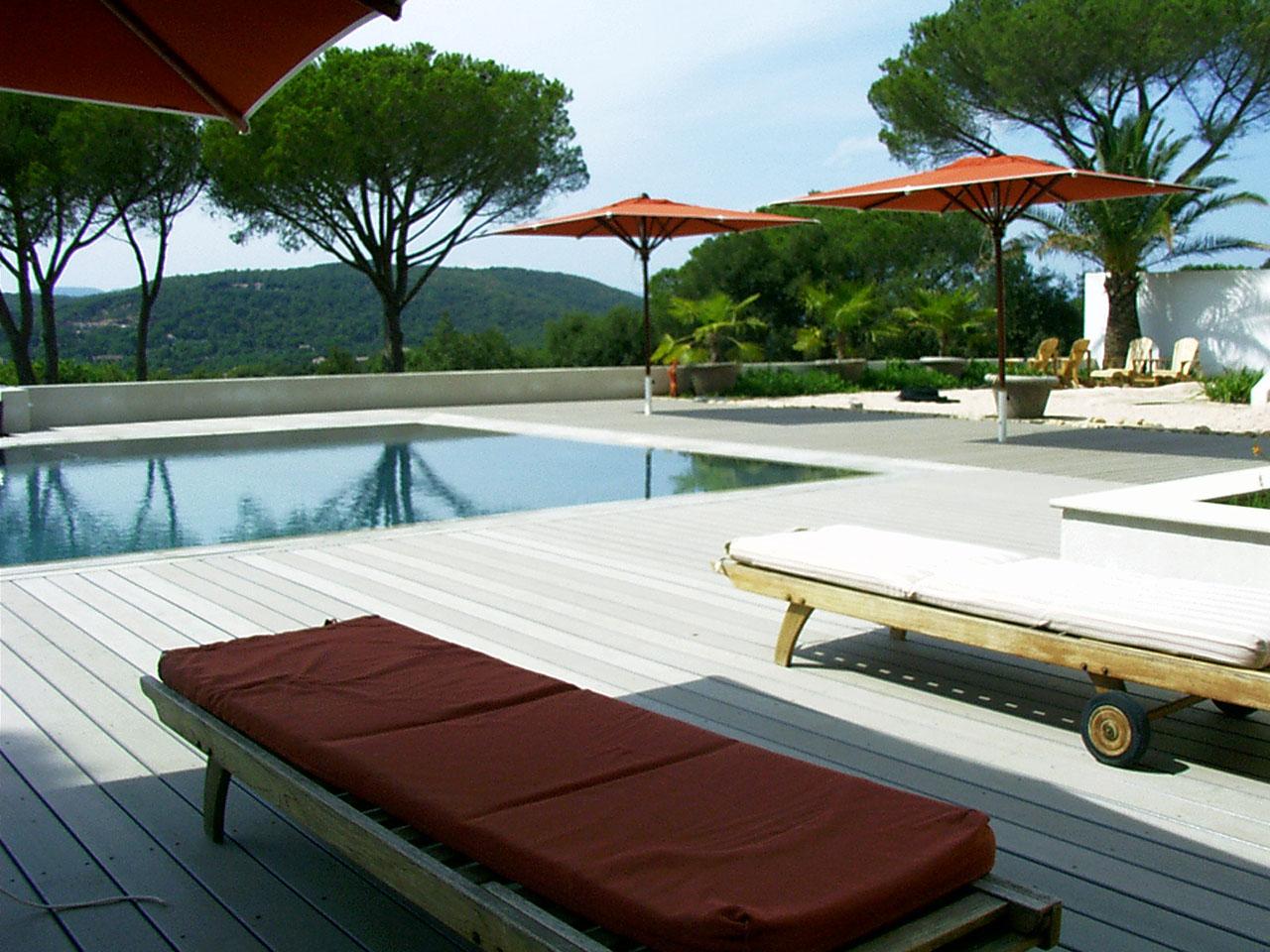 Poolumrandung aus WPC Dielen mit Holzliegen und roten Bezügen und Sonneschirmen