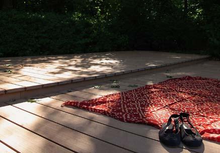 Stimmungsvolle Liegefläche mit WPC Terrassendielen im Schwimmbad mit Liegetuch