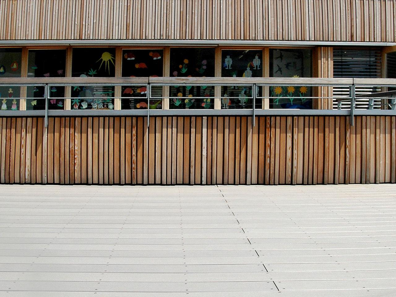 Massive, graue Terrassendielen aus WPC auf Terrasse vor Schulgebäude