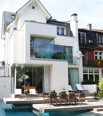 Wohnhaus mit höhenversetzen Terrassen auf denen Außendielen im modernen Design verlegt sind