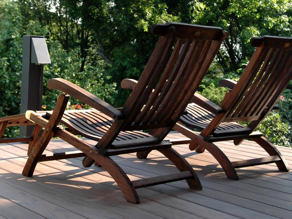 MYDECK Balkondielen in dunkelbraun mit Liegestühlen aus dunklem Holz und Blick ins Grüne