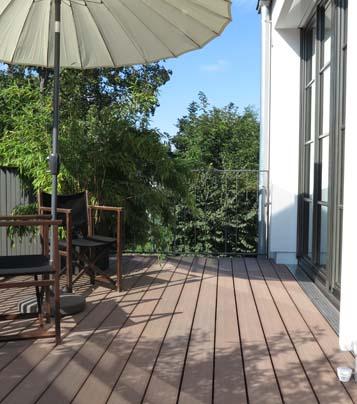 Balkongestaltung mit Sitzmöglichkeit, asiatischem Sonnenschirm und Blick in die Natur