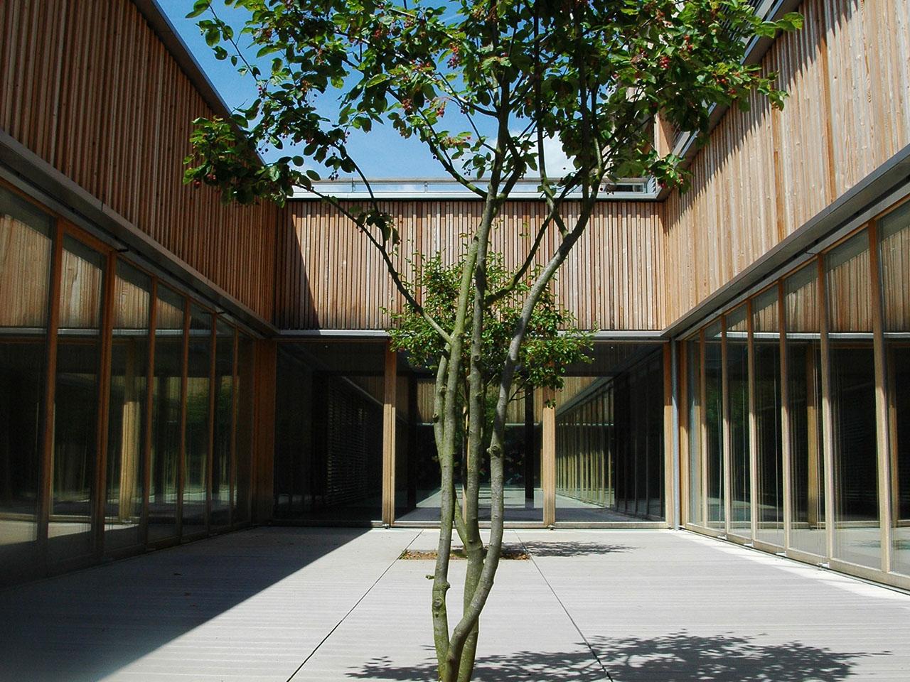 Blick in das Atrium einer Schule mit Holzfassade und grauen WPC Dielen