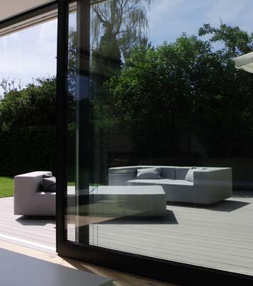 Blick auf moderne WPC Terrasse mit modernen Gartenmöbeln durch gläserne Schiebetür
