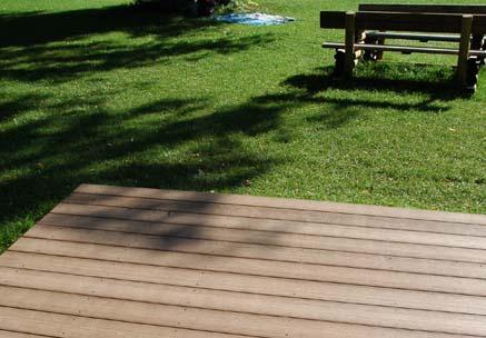Liegefläche aus splitterfreien WPC Außendielen auf einer Wiese bei Sonneschein im Schwimmbad