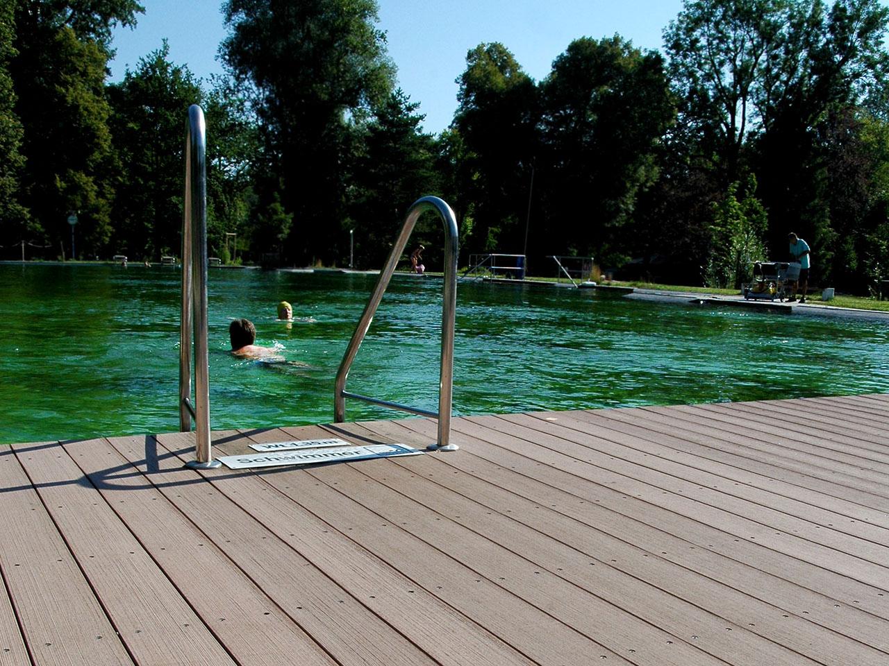 Rutschfeste WPC Poolumrandung in Schwimmbad mit Wasserleiter und Pool im Hintergrund