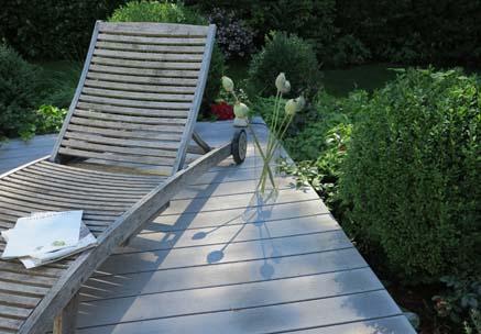 Terrassenhölzer der modernen Art auf gemütlich gestalteter Terrasse mit umgebendem Rasen