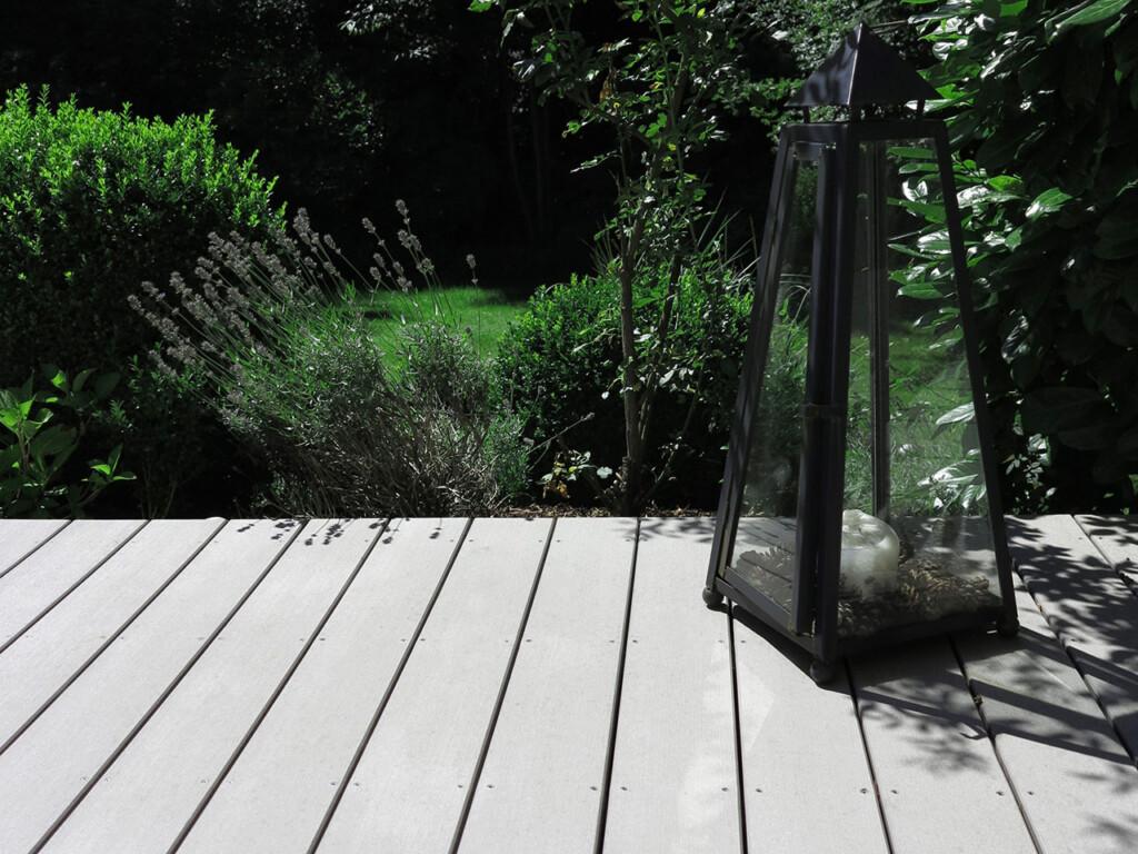 MYDECK vollprofile wpc in grau auf aussenfläche mit mediterraner Terrassengestaltung, Windlicht, Blick in den Garten