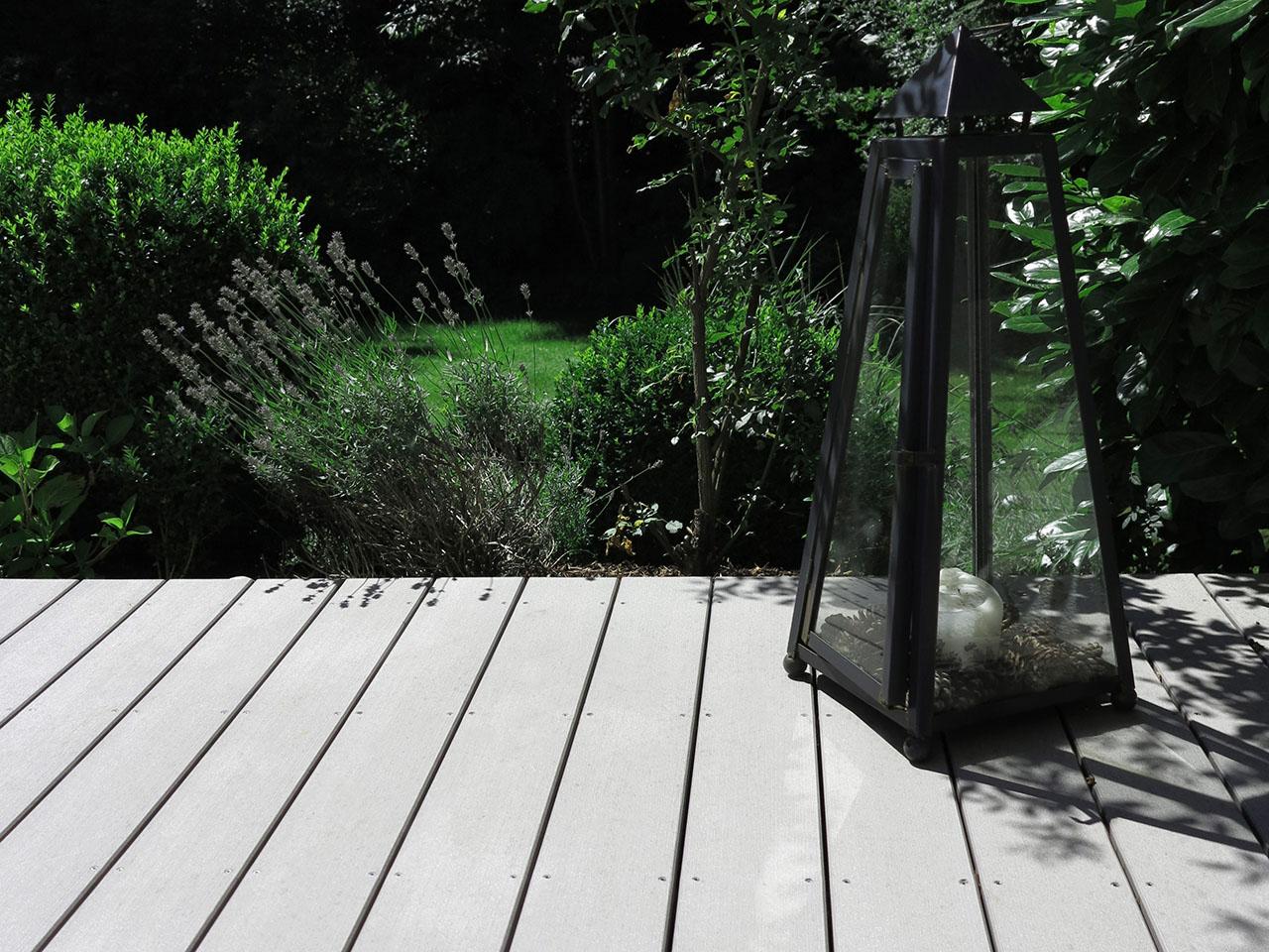 MYDECK Vollprofile auf einer Außenfläche verlegt und mit großem Windlicht dekoriert