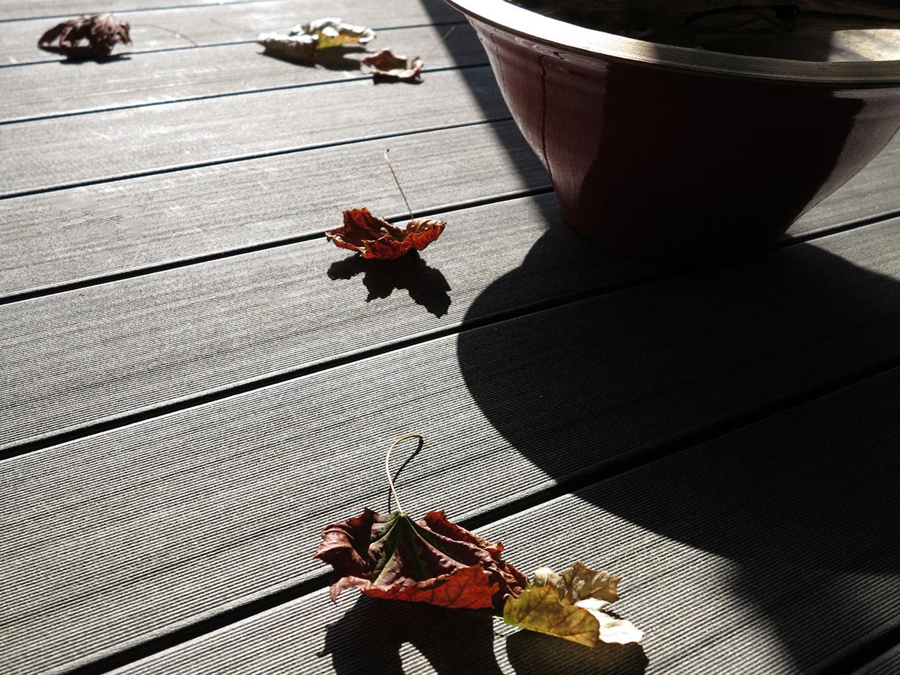 Wetterfeste WPC Balkondielen in anthrazit mit Herbstlaub auf den Dielen liegend