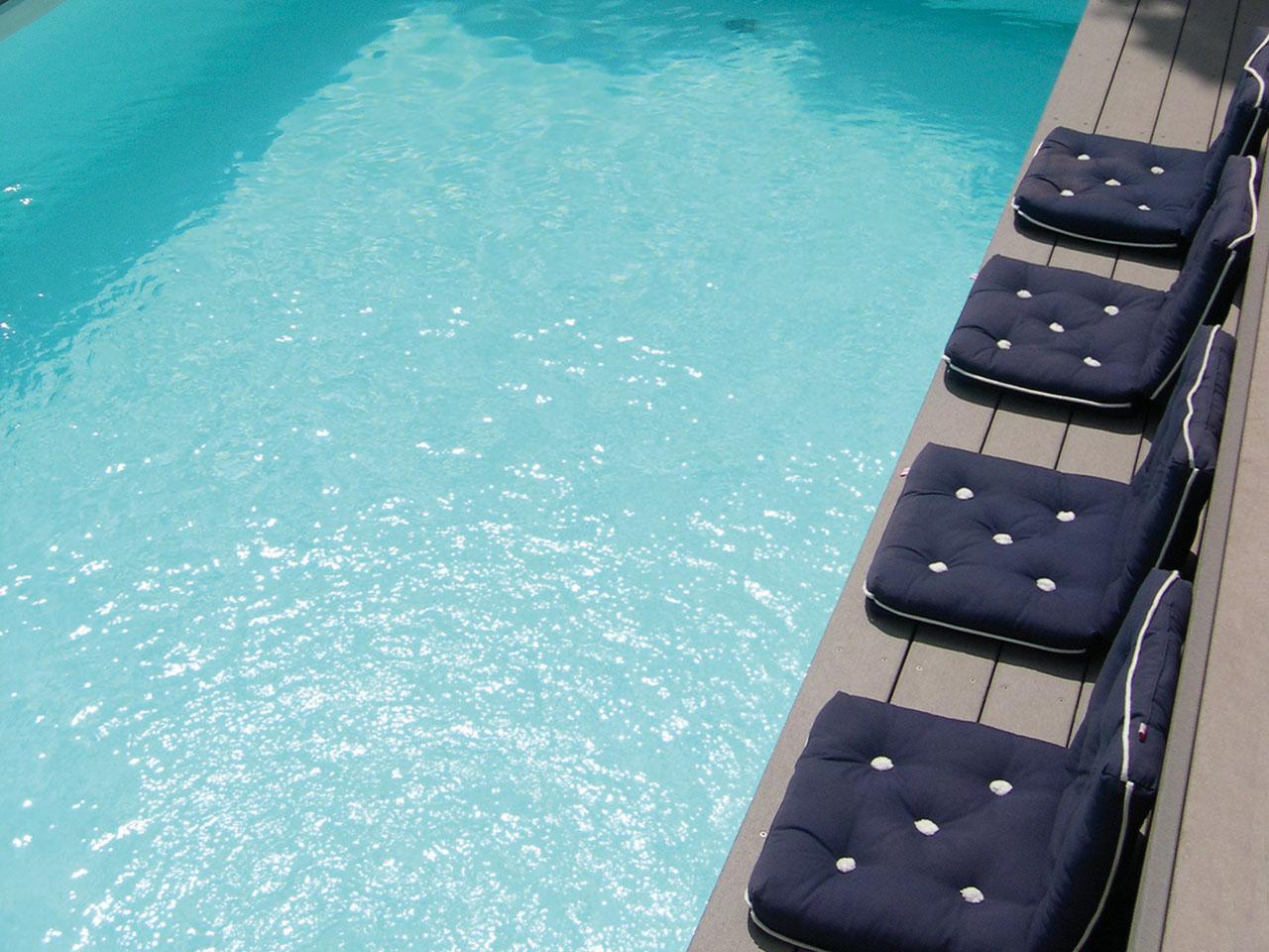 Poolumrandung aus grauen Barfußdielen mit Kissen zum Sitzen drauf und hellblauem Poolwasser