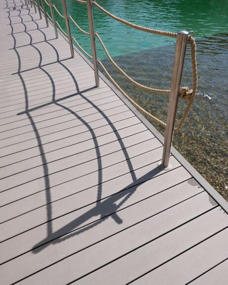Grauer Bodenbelag WPC in Schwimmbad, Steg mit WPC Dielen grenzt an Schwimmteich