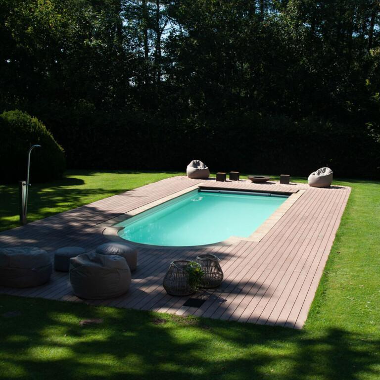 Die splitterfreien WPC Dielen grenzen an den Beckenstein des Pools und an den Rasen des Gartens.