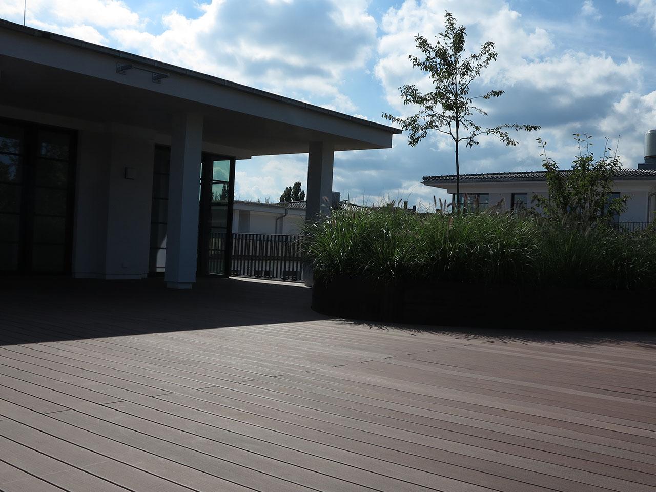 Braune Balkonhölzer aus WPC auf Penthouseterrasse mit Haus im Hintergund