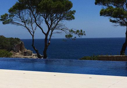 Blick von Poolumrandung mit WPC Terrassendielen auf Pool, Bäume und Meer