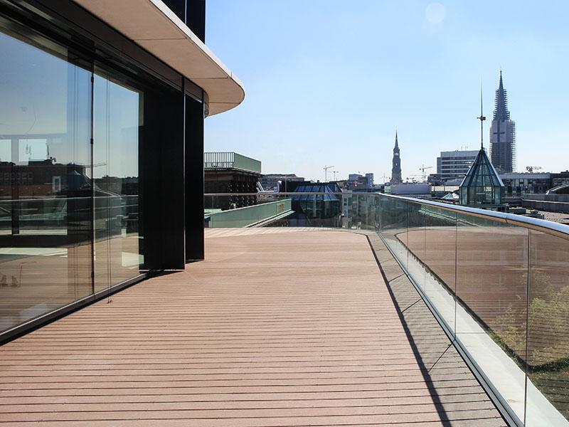 Hellbrauner Terrassenbelag auf geschwungener Terrasse mit Glasgeländer