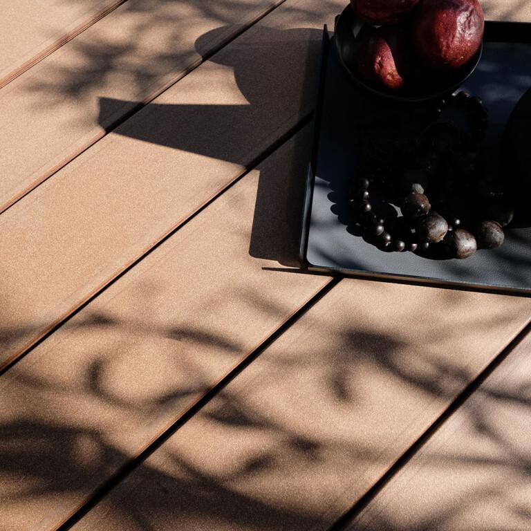 Dunkelbrauner WPC Terrassenbelag bei Sonnenschein mit Schatten einer Pflanze