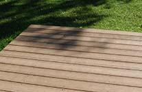 Terrassenbelag wpc in mittelbraun an grüne wiese angrenzend