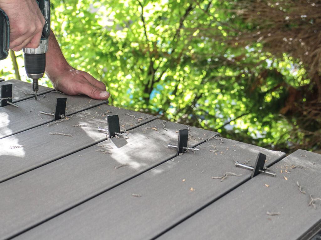 Die grauen Terrassenbohlen werden auf dem Foto Verschraubt, sind aber auch schraubenfrei verlegbar