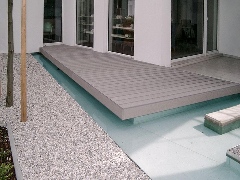Graue WPC Terrassenbretter auf Terrasse die Über Pool, bzw. Wasserfläche schwebt