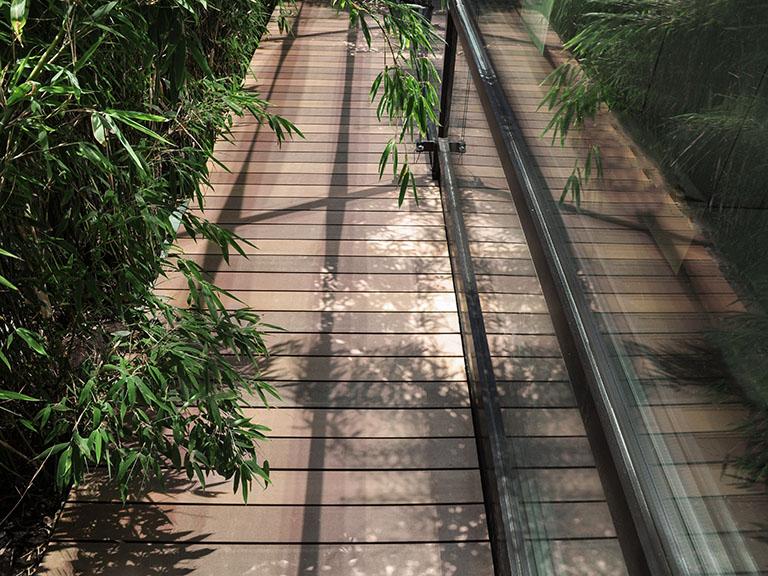 Terrassendielen WPC Holzoptik (mehrere Brauntöne wie Bangkirai) auf umlaufenden Balkon mit Bambus