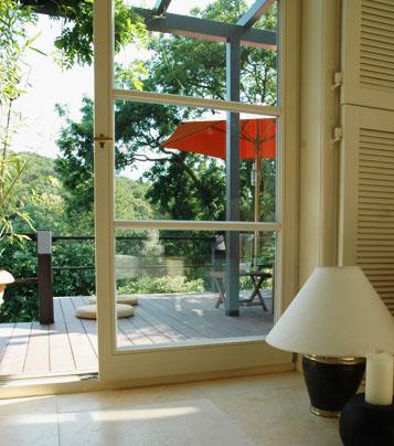 Blick aus moderne landhausschick Wohnung nach draußen auf Garten und moderne Terrassengestaltung