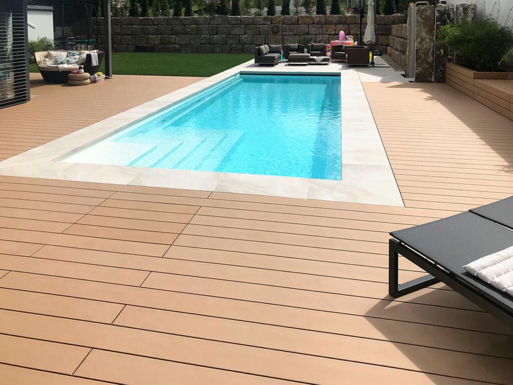 Splitterfreie WPC Poolumrandung in einladendem warmen Braunton umranden den Pool im Garten
