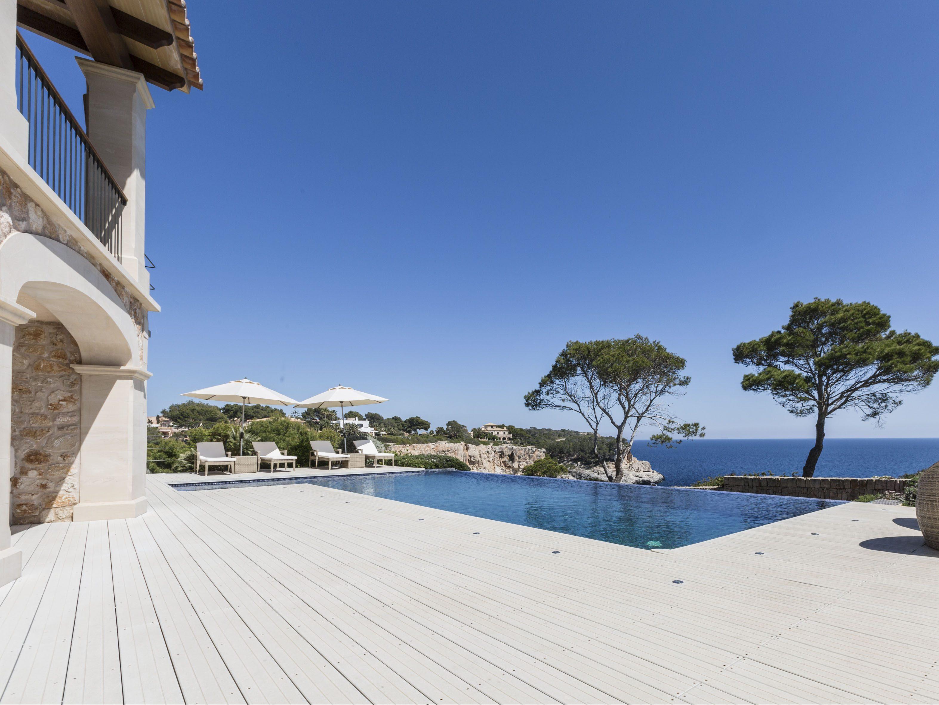 Die hellen WPC Dielen harmonieren mit den Möbeln auf der Terrasse und den Natursteinen der Villa und umranden bildschön den Pool.