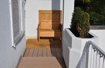 WPC Aussenplanke im Eingangsbereich eines modernen Hauses mit Sitzbank in der Sonne