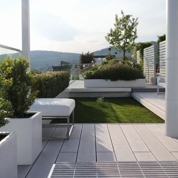 Moderne, großzügige Dachterrasse mit wetterfesten WPC Massivdielen in grau und Dachgarten