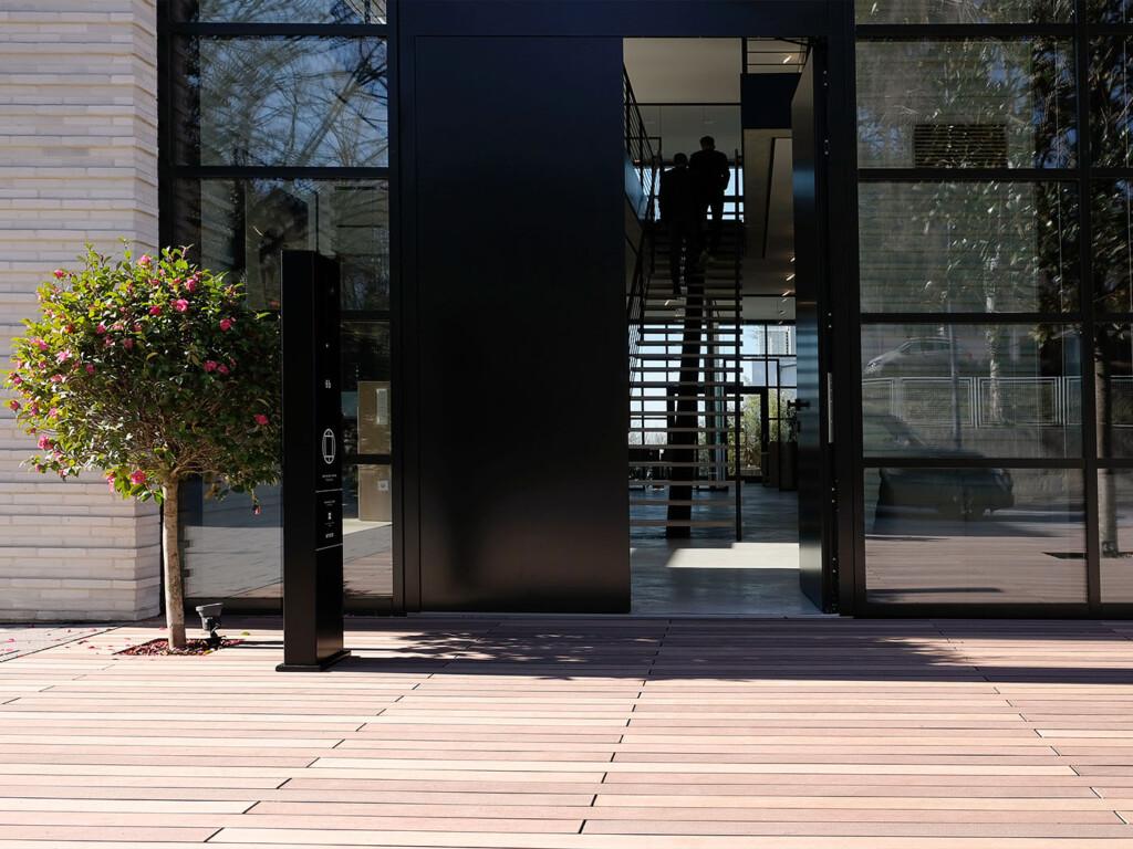 Terrasse mit WPC Dielen in verschedenen Brauntönen vor modernem Gebäude mit Glas und Backstein