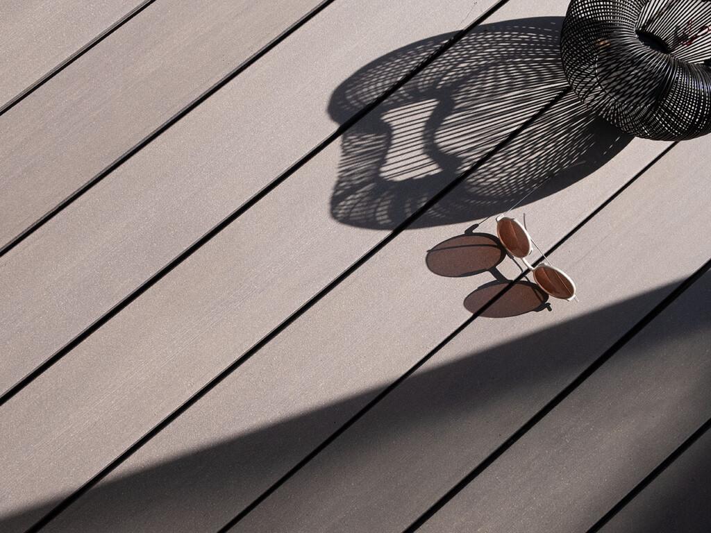 Graue WPC Dielen mit glatter Oberfläche bei Sonnenschein auf Terrasse (Produktbild)