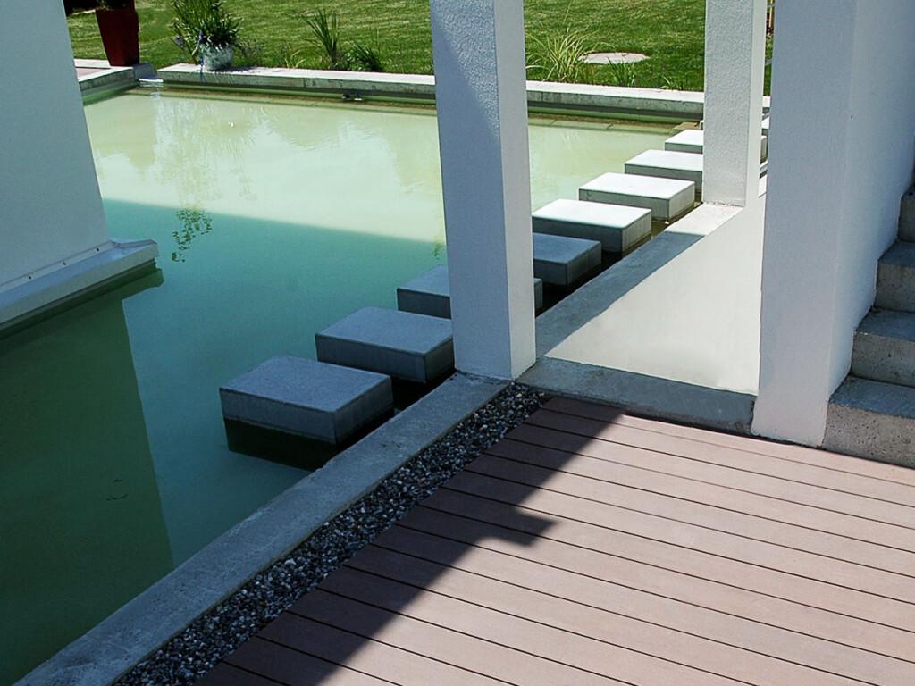 Betonstufen führen durch den Pool zu dem Garten und den Terrassen mit braunen WPC Dielen