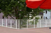 holzboden einer terrasse in braun mit matallgeländer und rotem sonnenschirm